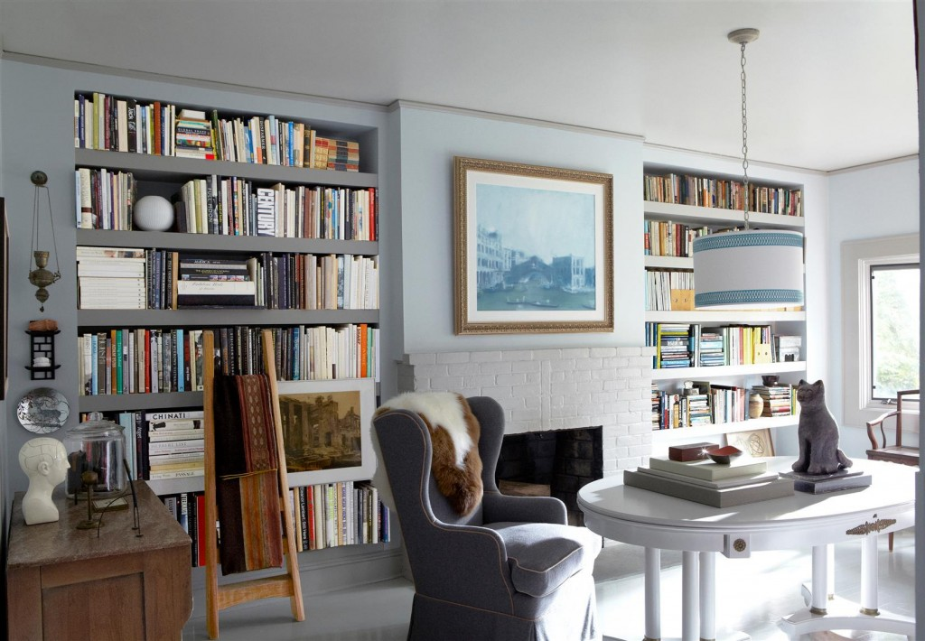 In the library, a pendant light fixture by Ro Sham Beaux hangs above a table bought at a flea market; the sheepskin throw was purchased at a charity auction, and the painting, After Tintoretto, is by Kevin Burger; the bookshelves are custom made, and the brick replace surround is painted in Benjamin Moore Aura in Lookout Point.