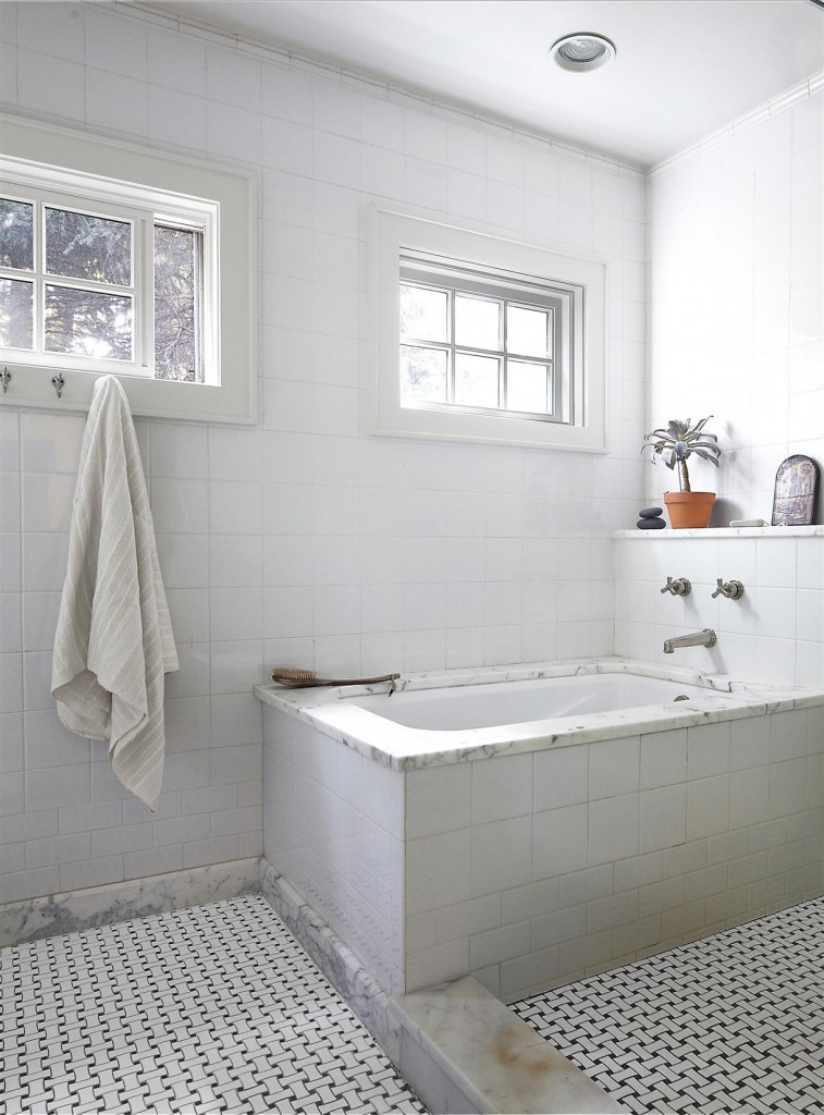 The tub and fittings in the master bath are by Waterworks, and the floor tiles are from Ann Sacks.