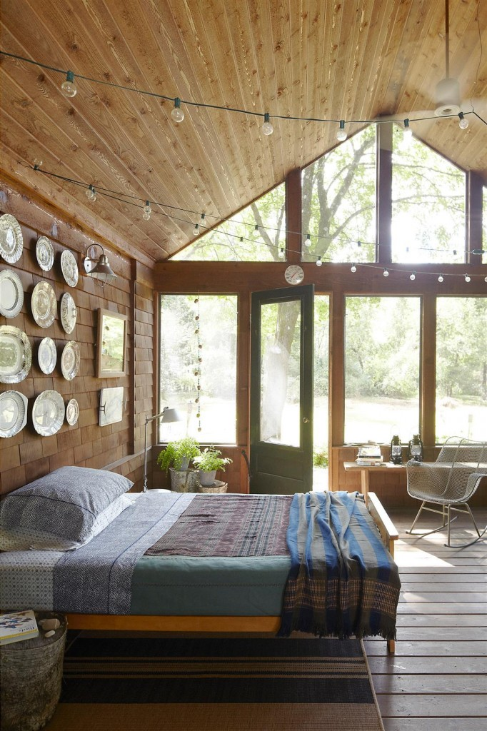 The screened porch's collection of transferware plates was purchased at yard sales, the bedding is by John Robshaw, and the rocker is by Harry Bertoia; the walls are stained cedar.