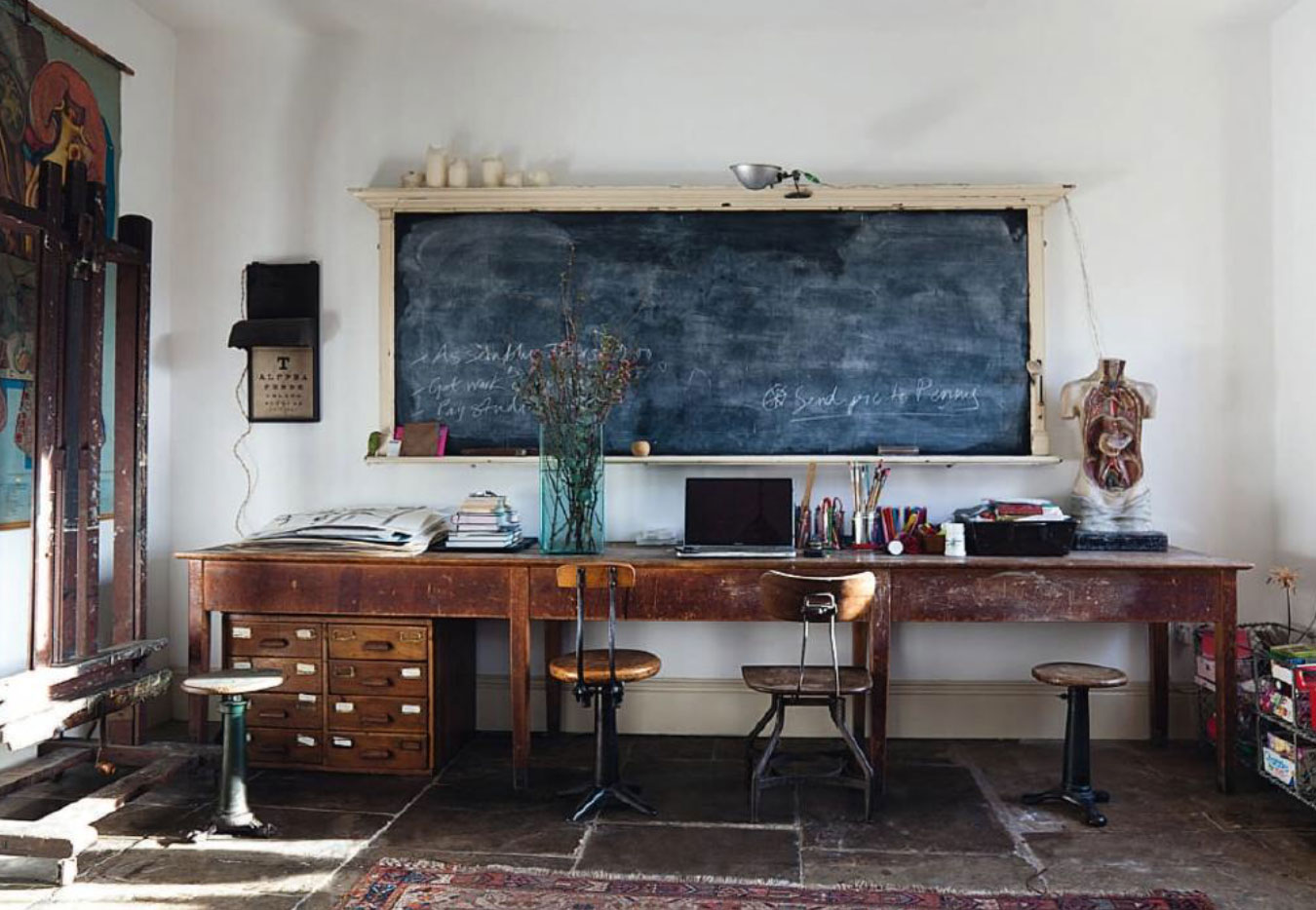 slabs on the floor and long wooden antique worktable as a desk