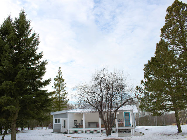 Exterior shot of small farmhouse nestled quietly in the snow.
