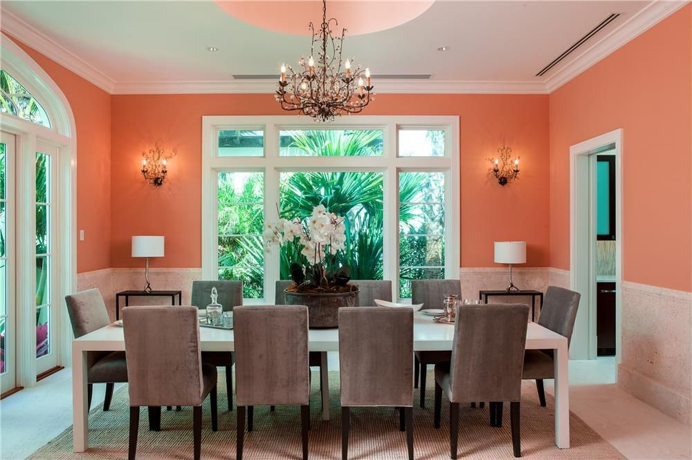 formal dining room with orange walls painted in sherwin williams lei