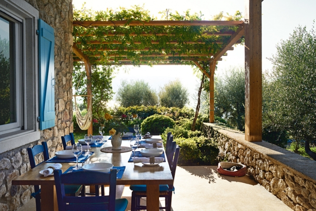 Under a vine, a stunning outdoor setting with blue chairs.