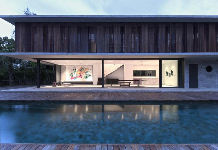 BANG SARAY HOUSE, DESIGNED BY ARCHITECTKIDD STUDIO IN THE SOUTH-EASTERN COASTAL AREA OF THAILAND, FOLLOWS A LENGTHWISE ARRANGEMENT. THE LARGE LIVING ROOM BLENDS WITH THE OUTDOOR AREAS THROUGH SLIDING GLASS DOORS