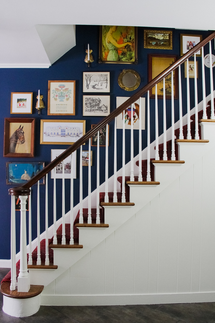 Benjamin Moore Washington Blue CW-630 stairwell wall with art and white stairs.