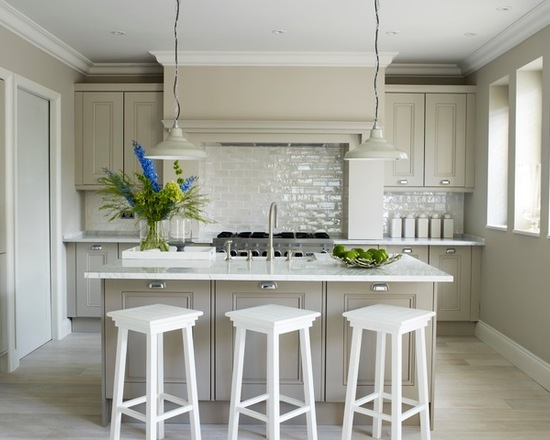 Transitional galley kitchen with recessed-panel cabinets, grey cabinets, beige splashback, subway tile splashback, light hardwood floors and an island. cabinet color= farrow and ball: elephant's breath no. 229. via Peach Studio