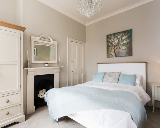 Farrow & Ball Elephant's Breath painted walls in this mid-sized traditional guest bedroom. The Humber with grey walls, carpet, a standard fireplace and a metal fireplace surround.