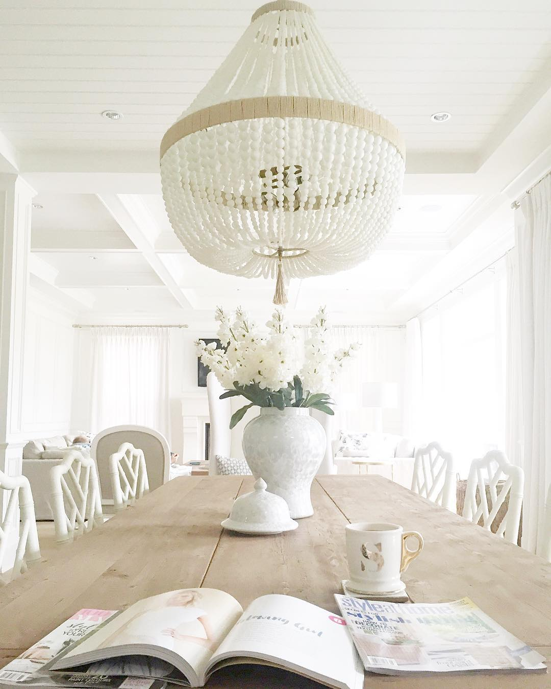 White painted wood paneled ceiling, white walls, blonde wood raw table.