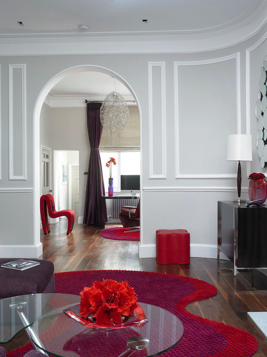 Blend old and new - Have an historic home but modern tastes? Don't try to downplay your home's period features – emphasise them, as this designer has, to create an eye-catching contrast with your contemporary furniture. Love the mixture of red accents with the gray wall color. Walls painted in Elephant's Breath. via The Room Company