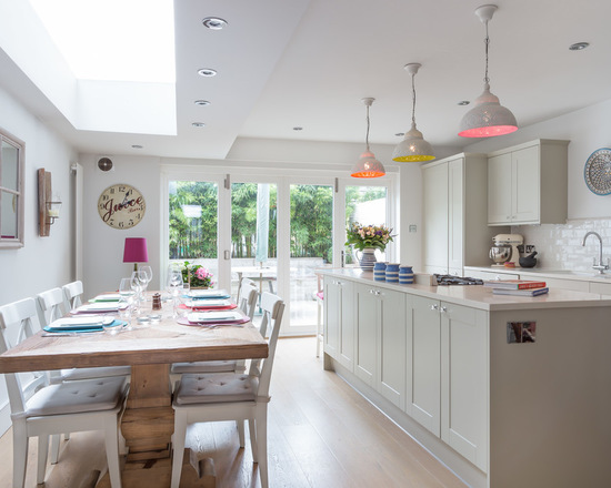 This is an example of a transitional kitchen in London with shaker cabinets, grey cabinets, white splashback, subway tile splashback and light hardwood floors. Kitchen cabinets painted in Elephant's Breath