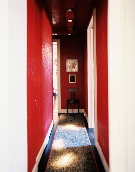 Red walls and a leopard-print carpet runner in a long hallway Details: Red Eclectic-Modern Hallway