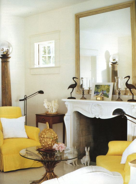 Fireplace with mirror and two yellow armchairs.