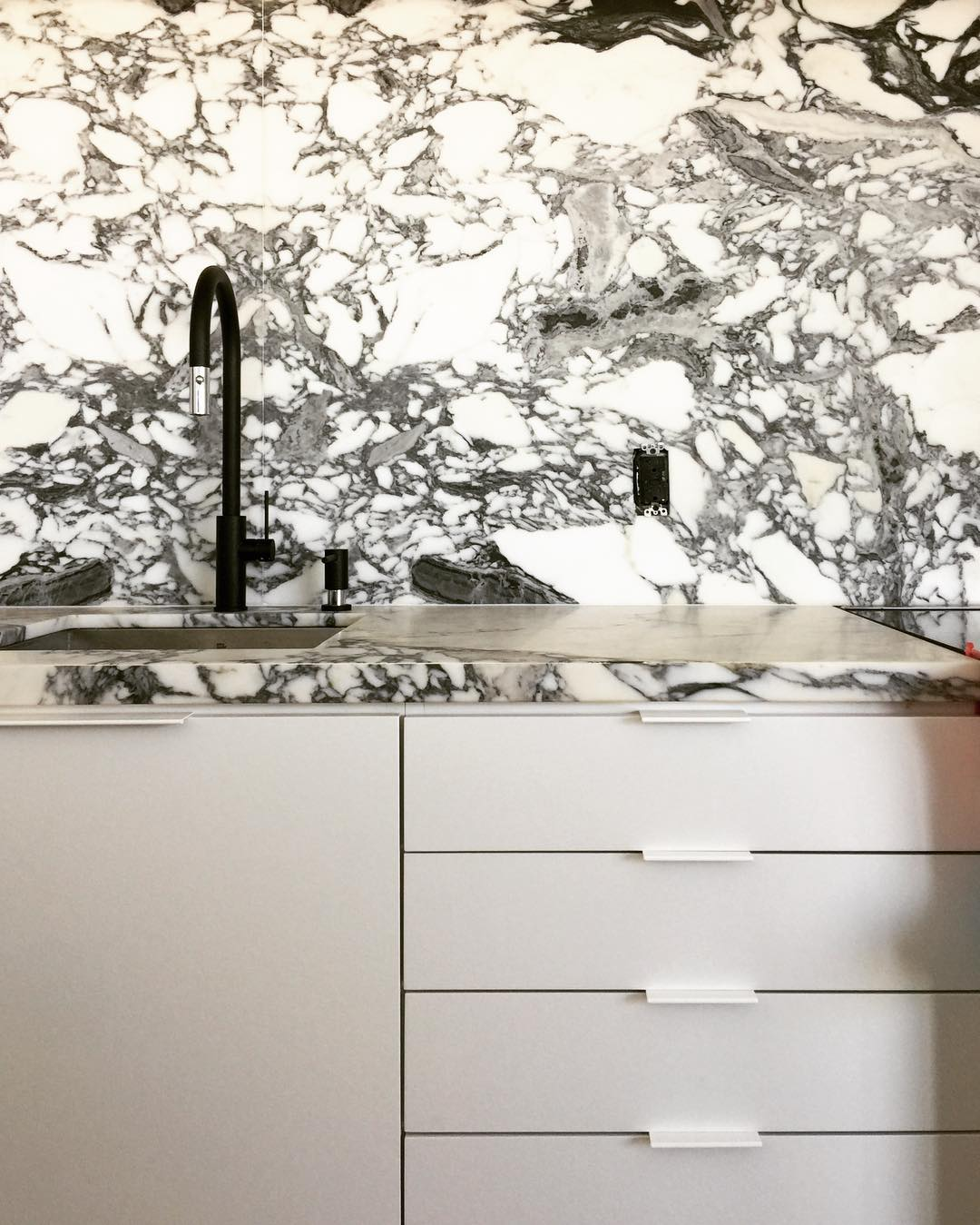 Black and White Marble Kitchen Color Scheme. Timber herringbone flooring kitchen, black taps and hardware.