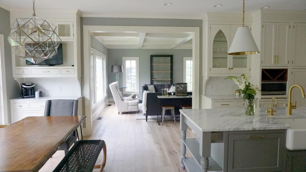 A kitchen in white and shades of gray with the kitchen island painted in Chelsea Gray by Benjamin Moore