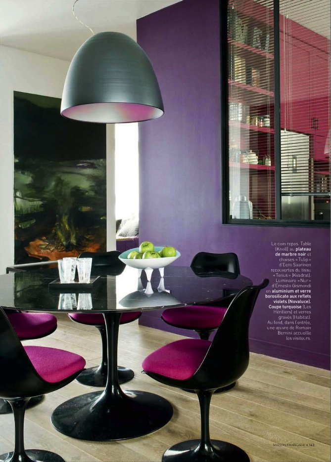 Saturated purple dining room walls and hot pink and black dining chairs, contempoary dining room in a purple and pink color scheme.