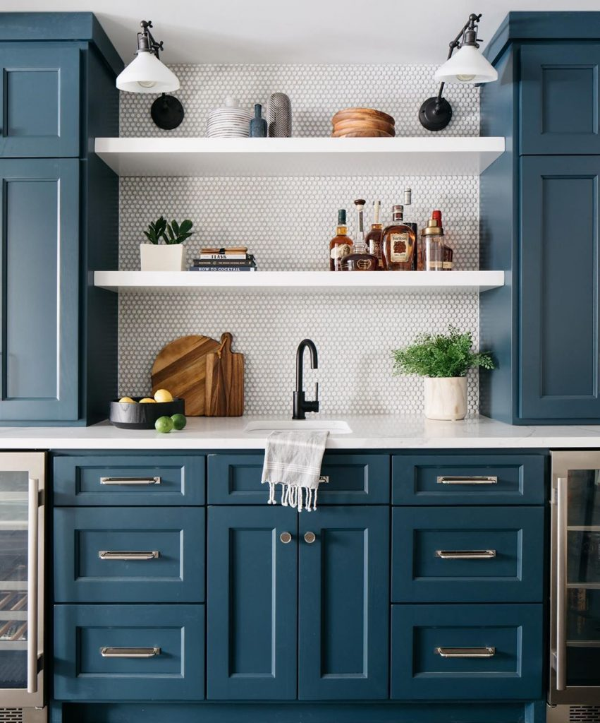 Kitchen with navy blue kitchen cabonets and penny rounds splashback