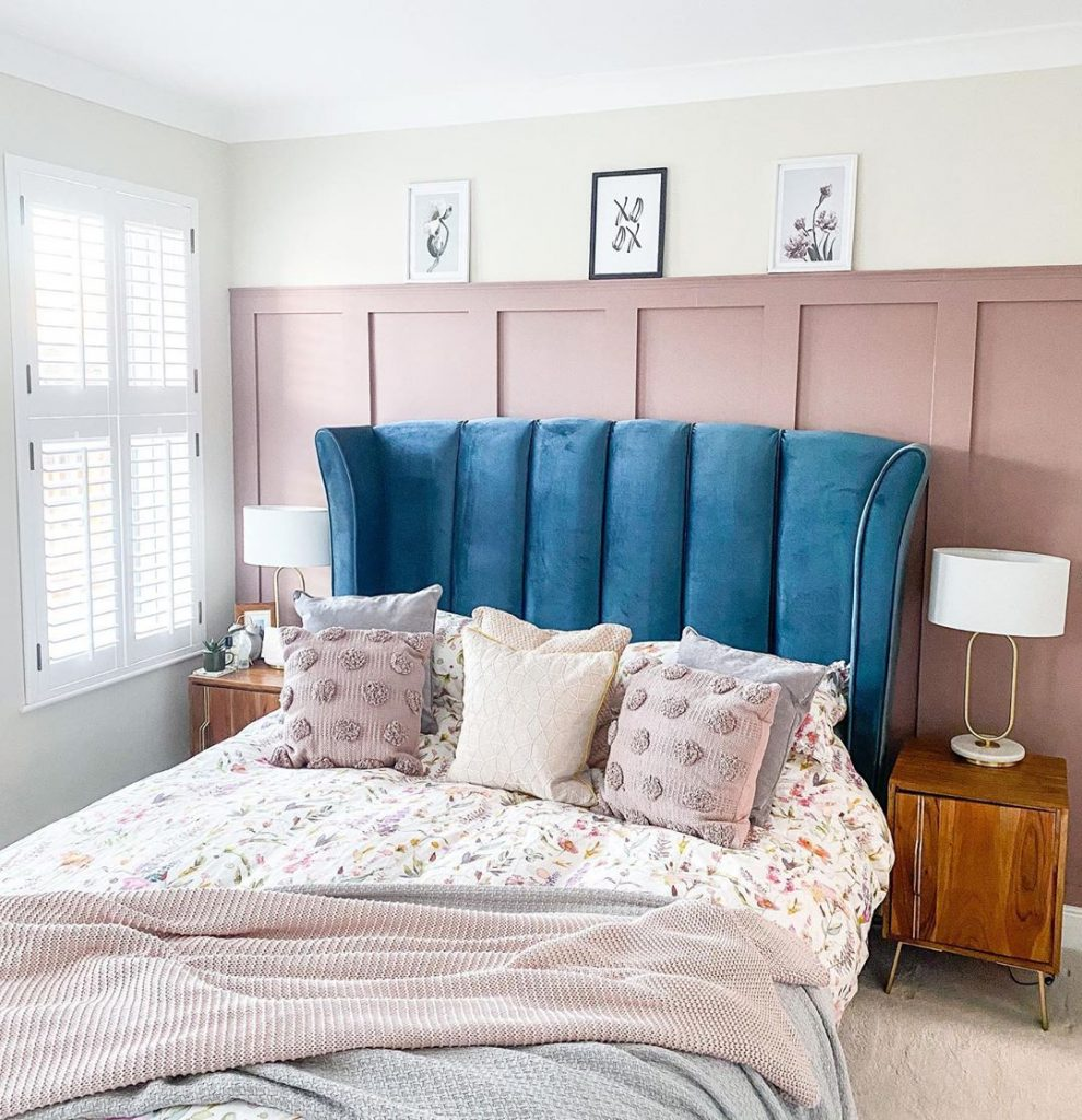 Farrow & Ball Sulking Room Pink feature wall master bedroom. Blue velvet headboard. Romantic bedroom design interior with a blue and mauve pink color scheme