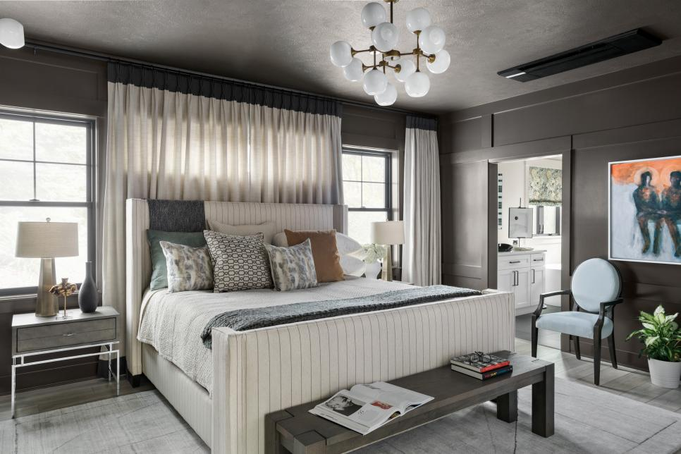Mixing creamy tones from the upholstered pinstriped bed frame to the soft layers of bedding creates an inviting focal point.